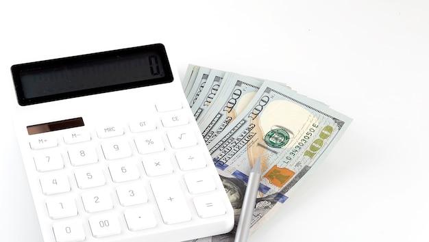 Calcolatrice e dollari isolati su sfondo bianco