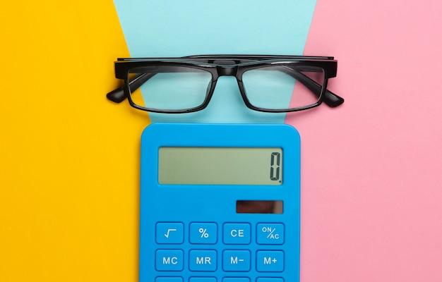 Calcolatrice e bicchieri colorati. segretario, economista o concetto di impiegato.