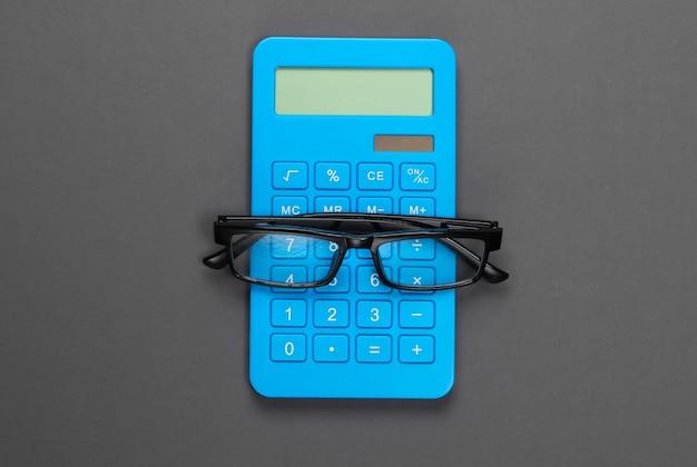 Calcolatrice e bicchieri su grigio. segretario, economista o concetto di impiegato