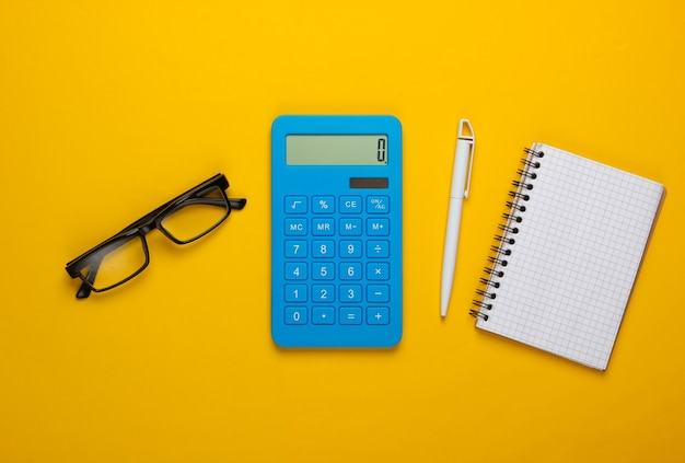 Calcolatrice e bicchieri, taccuino su colore giallo. segretario, economista o concetto di impiegato. Foto Premium