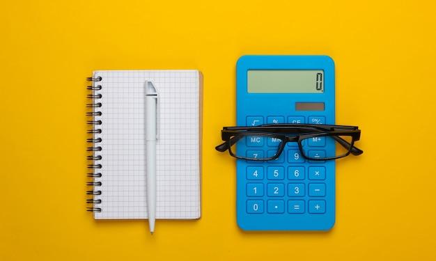 Calcolatrice e bicchieri, taccuino su colore giallo. segretario, economista o concetto di impiegato.