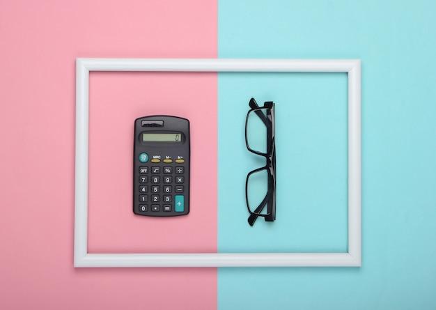 Calcolatrice e bicchieri in cornice bianca su superficie pastello blu rosa