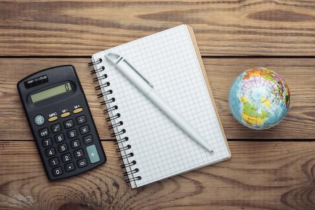 Calcolatrice, globo e taccuino sulla tavola di legno. vista dall'alto. minimalismo. concetto di educazione, geografia