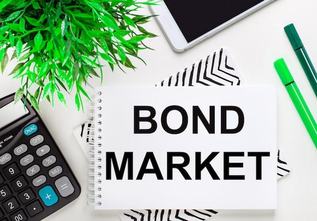 Calcolatrice, pianta verde, telefono, pennarello, taccuino con il testo bond market sul desktop