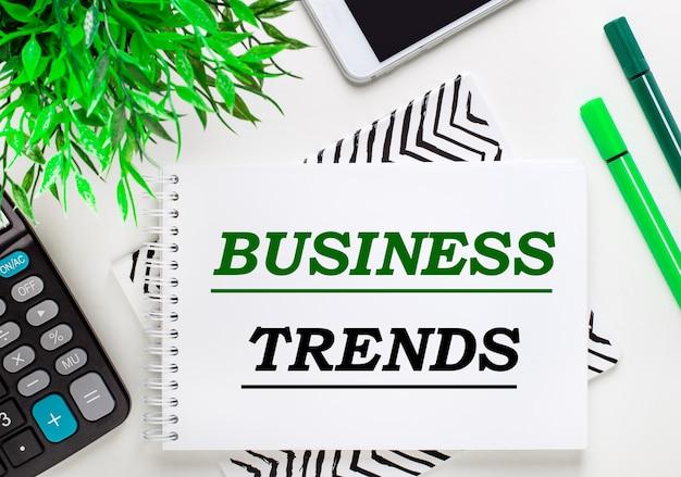 Calcolatrice, pianta verde, telefono, pennarello, notebook con il testo business trends sul desktop. disposizione piatta.