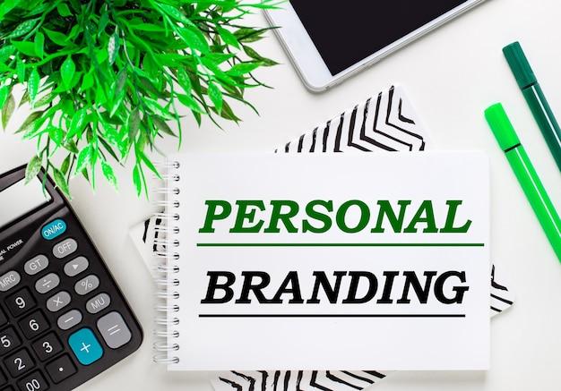 Calcolatrice, pianta verde, telefono, pennarello, taccuino con il testo personal branding sul desktop. disposizione piatta.
