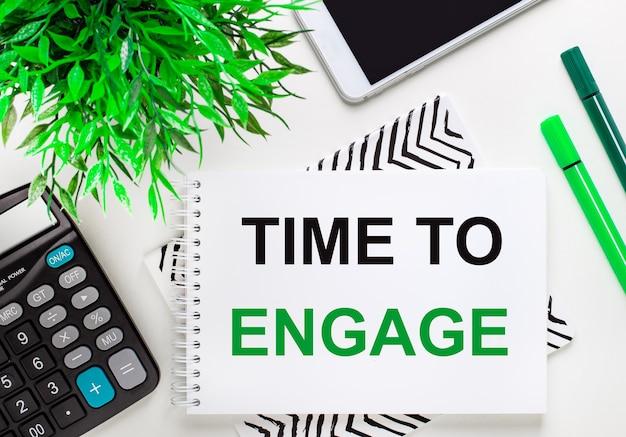 Calcolatrice, pianta verde, telefono, pennarello, taccuino con il testo time to engage sul desktop
