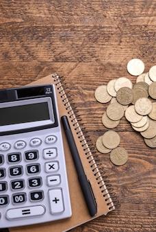 Tastiera calcolatrice, monete d'oro, penna e taccuino su un pavimento di legno. vista dall'alto. copia spazio