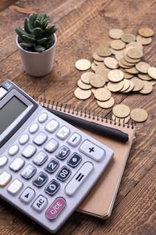 Tastiera calcolatrice, monete d'oro, penna e taccuino su un pavimento di legno