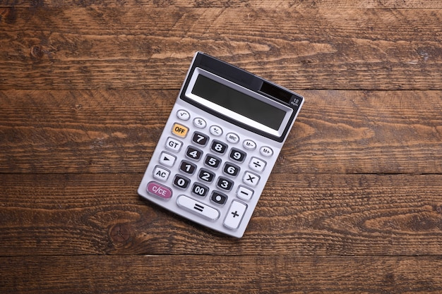 Tastiera calcolatrice su uno sfondo di pavimento in legno. vista dall'alto. copia spazio
