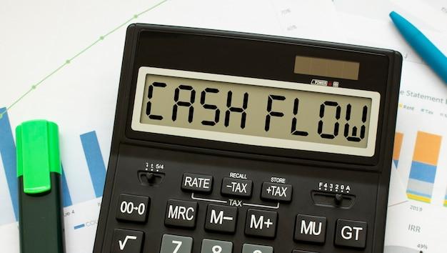 Una calcolatrice etichettata flusso di cassa si trova sui documenti finanziari in ufficio. concetto di affari.