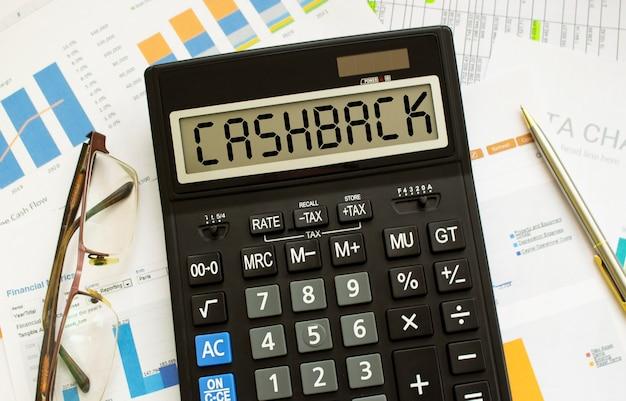 Una calcolatrice etichettata cashback si trova sui documenti finanziari in ufficio. concetto di affari.