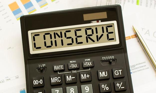 Una calcolatrice etichettata conserve si trova sui documenti finanziari in ufficio. concetto di affari.
