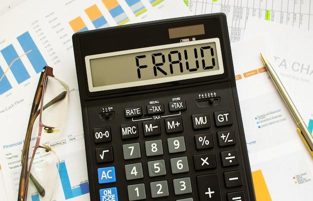 Una calcolatrice etichettata frode si trova sui documenti finanziari in ufficio. concetto di affari.