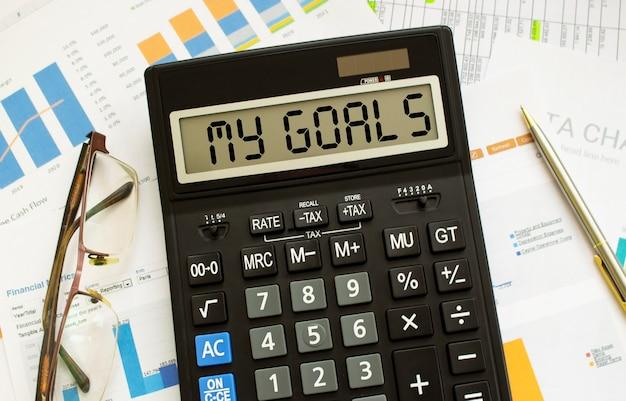 Una calcolatrice etichettata i miei obiettivi si trova sui documenti finanziari in ufficio. concetto di affari.