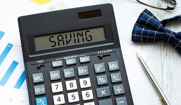 Una calcolatrice con l'etichetta risparmio si trova sui documenti finanziari in ufficio. concetto di affari.
