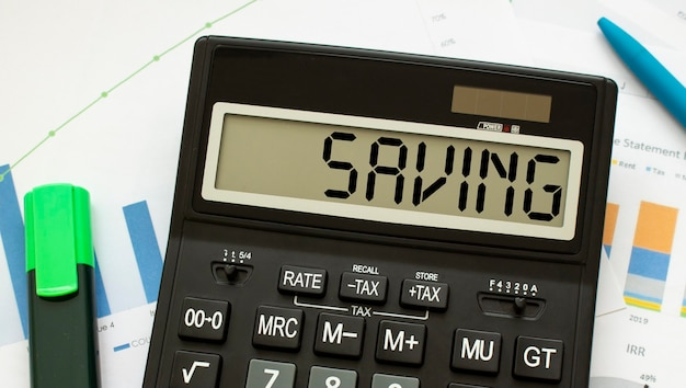 Una calcolatrice con l'etichetta risparmio si trova sui documenti finanziari in ufficio.