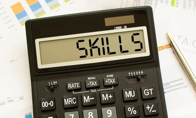Una calcolatrice con l'etichetta skills si trova sui documenti finanziari in ufficio. concetto di affari.