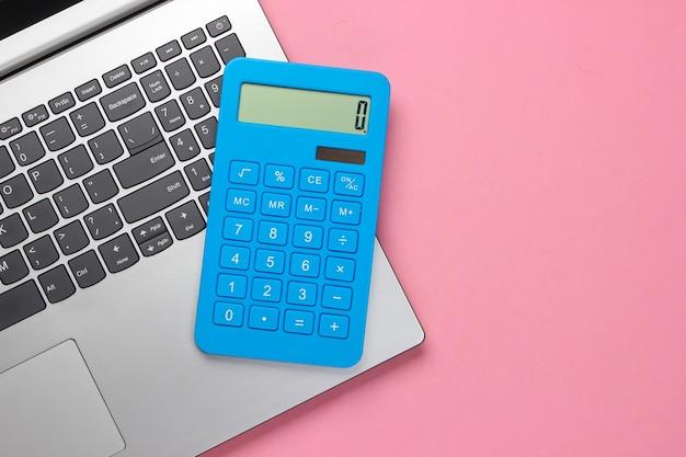 Calcolatrice e laptop su pastello rosa