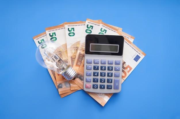 Calcolatrice e lampadina sul concetto di spesa energetica dei soldi