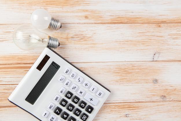 Calcolatrice e lampadine sulla scena in legno