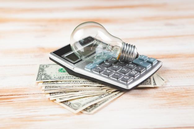 Calcolatrice, soldi e lampadina sulla scena in legno