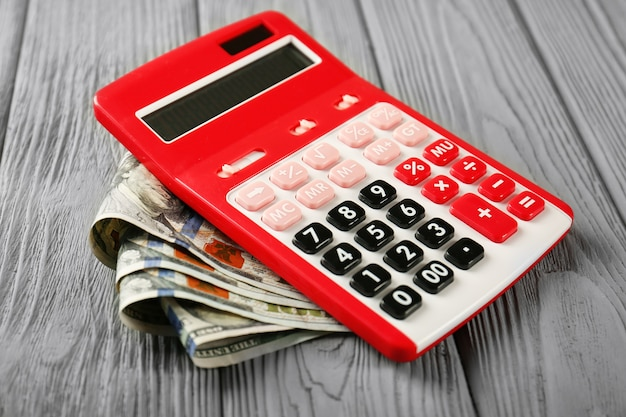 Calcolatrice e soldi sul tavolo di legno