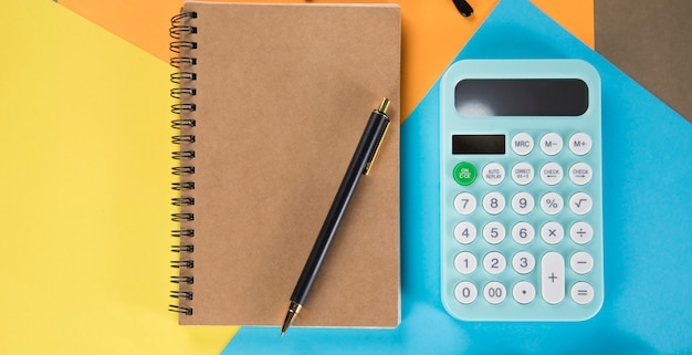 Calcolatrice e taccuino su pezzi di carta multicolori. concetto di desktop