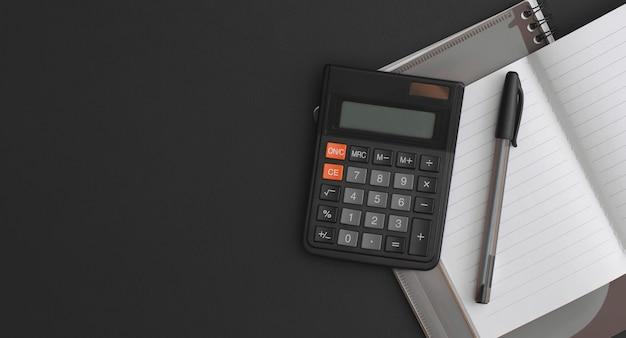 Calcolatrice, taccuino, penna su fondo in pelle nera. vista dall'alto con copia spazio. composizione piatta.