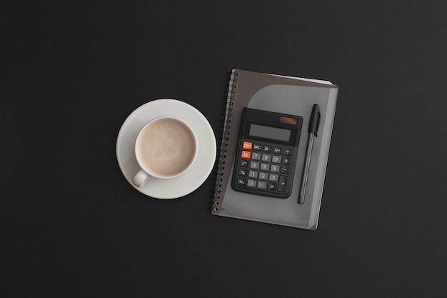Penna per taccuino calcolatrice e una tazza di caffè su fondo in pelle nera