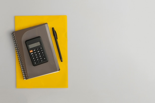 Calcolatrice, taccuino e penna su sfondo grigio