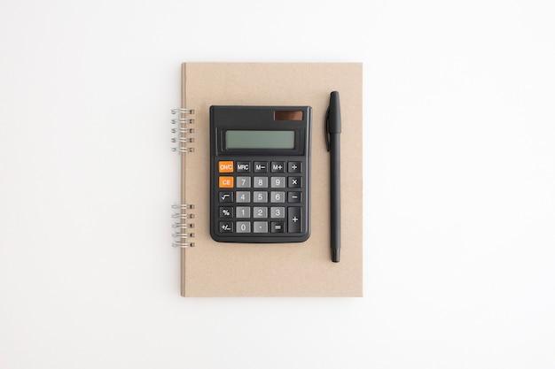 Calcolatrice, taccuino e penna su sfondo bianco