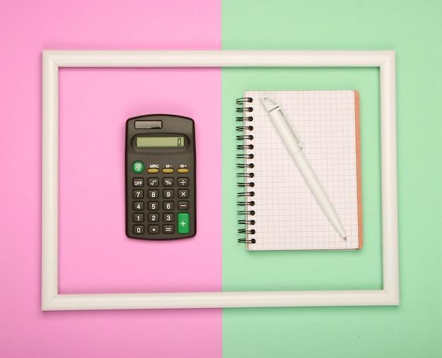 Calcolatrice e taccuino in cornice bianca su superficie pastello verde rosa