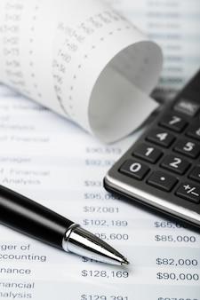 Calcolatrice e nastro di carta con dati finanziari