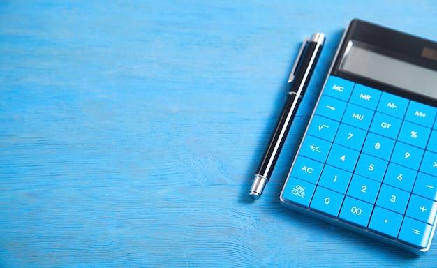 Calcolatrice e penna su sfondo blu