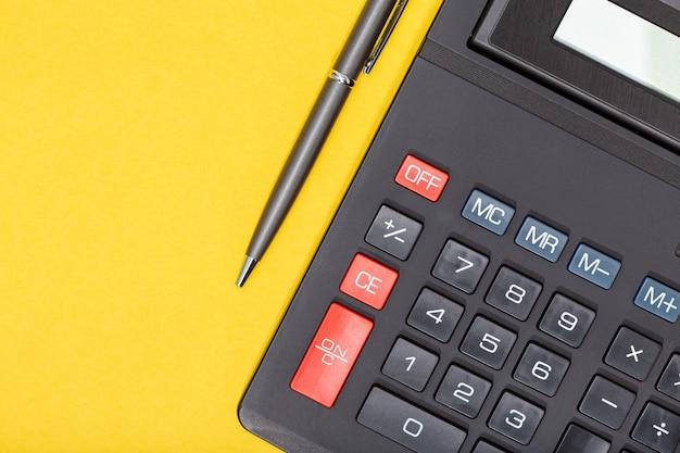 Calcolatrice e penna su sfondo giallo. sfondo di concetto di economia o affari