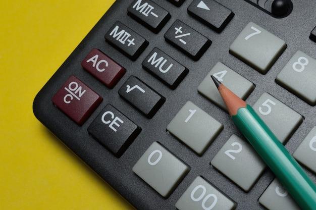 Calcolatrice e matita giacciono su uno sfondo giallo. avvicinamento.