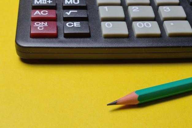 Calcolatrice e matita giacciono su un tavolo giallo. avvicinamento.
