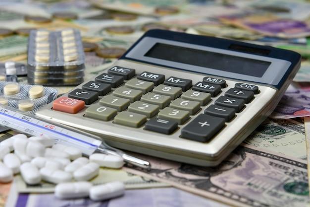 Calcolatrice, pillole e termometro sul delle varie banconote in valuta nazionale. la disponibilità medica e l'aumento delle spese mediche.
