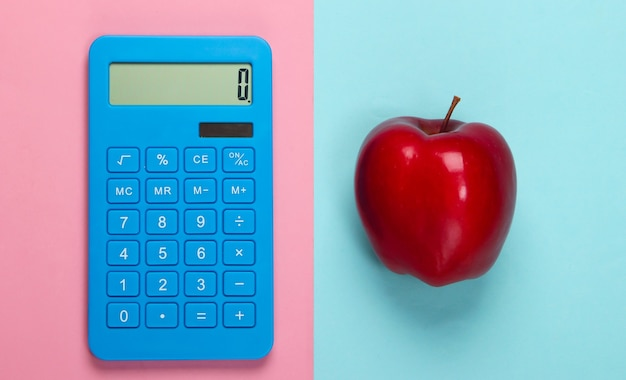 Calcolatrice e mela rossa su un pastello bluepink. concetto di educazione