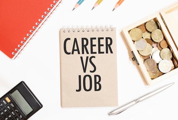 Calcolatrice, blocco note rosso, tre matite colorate, penna d'argento e taccuino marrone con testo carriera vs lavoro