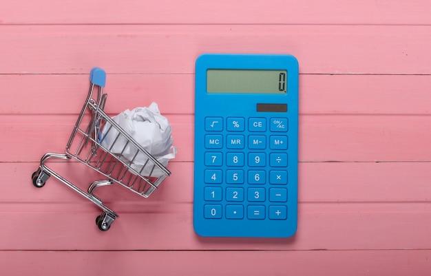 Calcolatrice e carrello della spesa con una palla di carta stropicciata su un legno rosa