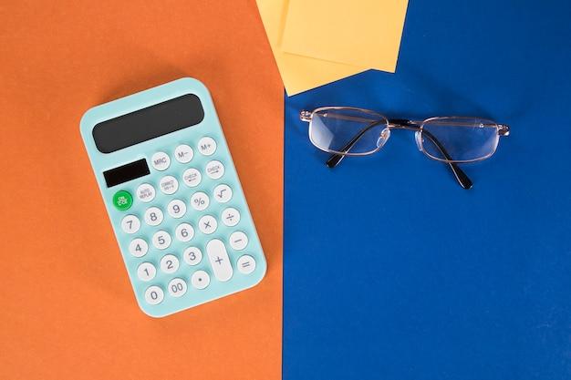 Calcolatrice, adesivi e bicchieri sulla scena colorata
