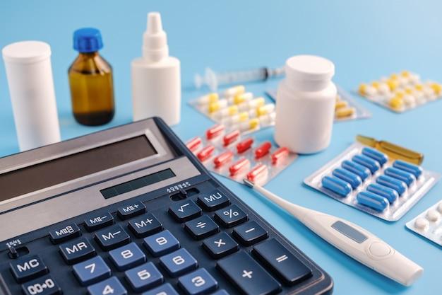 Calcolatore, termometro e mucchio di droghe su sfondo blu.