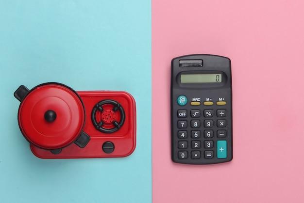 Calcolatrice e fornello giocattolo con padella su un pastello blu-rosa
