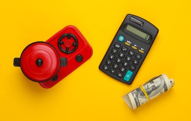 Calcolatrice e fornello giocattolo con pentola e banconote da un dollaro su giallo.