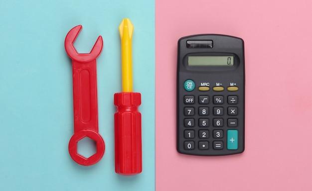 Calcolatrice e strumento di lavoro giocattolo su un pastello blu-rosa.