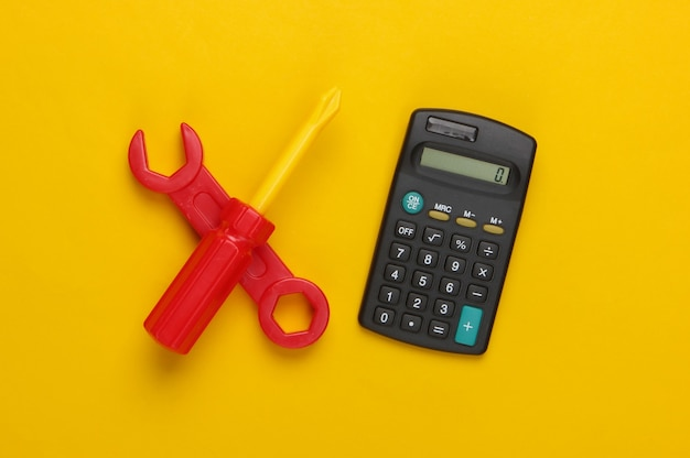 Calcolatrice e strumento di lavoro giocattolo su giallo. calcolo del costo di riparazione.