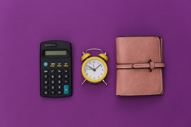 Calcolatrice, portafoglio e sveglia su sfondo viola.