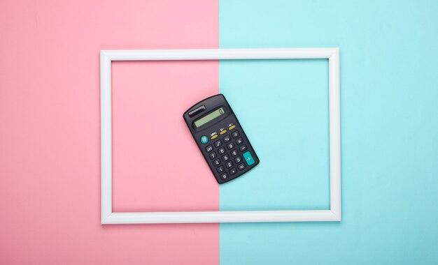 Calcolatrice in cornice bianca su superficie pastello blu rosa